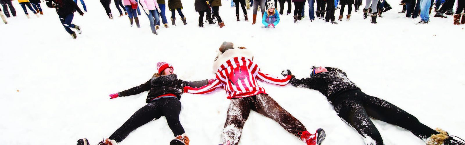Students lying in the snow holding Bucky's hands